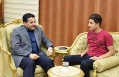 O ministro de Interior do Iraque, Qasim al-Araji, se encontra com o adolescente iraquiano Osama Bin Laden em Bagdá - STRINGER / AFP