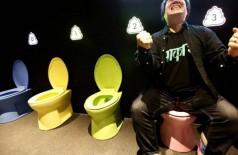 Um visitante do 'museu do cocô', no Japão, fingindo que está usando o banheiro na exposição - Foto: KIM KYUNG-HOON / REUTERS