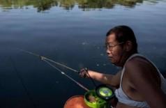 Chinês pesca com a camiseta enrolada até o peito: agora está proibido Foto: AFP