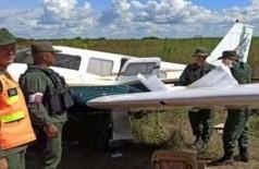 Policiais ao lado da aeronave que era ocupada pelos suspeitos. (Foto: Elpitazo)