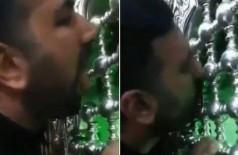 Fiel xiita beija e lambe portão de entrada de mesquita no Irã (Foto: Reprodução/Twitter)