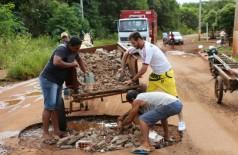 Homens jogam entulhos na tentativa de improvisar um tapa-buracos em trecho da Via Parque (Eliel Oliveira)
